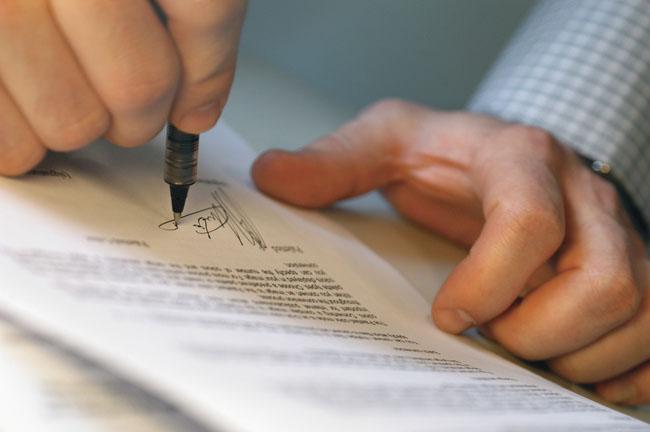 Man's Hands Signing Document - Contabilidade em Brasília | Vértice Contadores e Associados S/S Ltda.